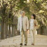 パリの並木道を歩くシニア夫婦