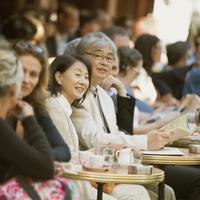 パリのサンジェルマン・デ・プレのカフェで微笑むシニア夫婦