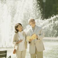噴水の前でガイドブックを持ち微笑むシニア夫婦