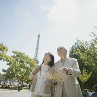 エッフェル塔の前でガイドブックを持ち微笑むシニア夫婦