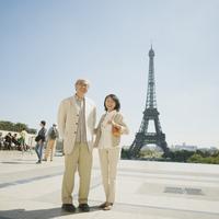 エッフェル塔の前で微笑むシニア夫婦