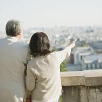 パリの街並みを眺めるシニア夫婦の後姿
