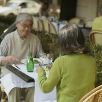 パリのレストランでフレンチ料理を食べるシニア夫婦