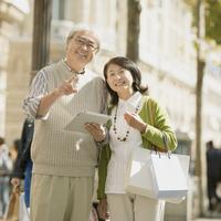 タブレットPCを持ちパリの街を歩くシニア夫婦