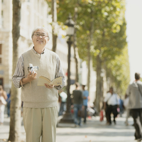 カメラとガイドブックを持ちパリの街を歩くシニア男性 20027011214| 写真素材・ストックフォト・画像・イラスト素材|アマナイメージズ