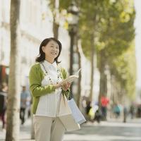 ガイドブックを持ちパリの街を歩くシニア女性
