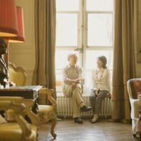 パリのアパルトマンの窓辺に座り談笑をするシニア夫婦