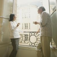パリのアパルトマンのベランダで談笑をするシニア夫婦