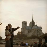 ノートルダム大聖堂の前で指差しをするシニア夫婦