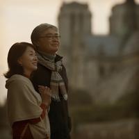 ノートルダム大聖堂の前で微笑むシニア夫婦