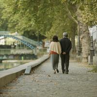 パリのサン・マルタン運河のほとりを歩くシニア夫婦の後姿