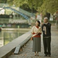 パリのサン・マルタン運河のほとりを歩くシニア夫婦