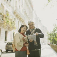 パリの街でガイドマップを見るシニア夫婦