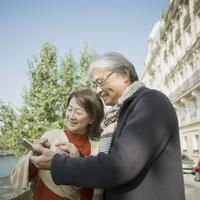 パリの街でスマートフォンを見るシニア夫婦