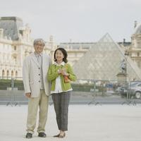 ルーブル美術館の前で微笑むシニア夫婦