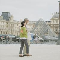 ルーブル美術館の前を歩くシニア夫婦