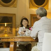 パリのアパルトマンでワインを飲むシニア夫婦