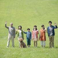 草原で手を振る3世代家族