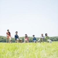草原で椅子に座る3世代家族