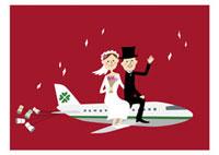 飛行機に乗ってハネムーンに向かう新郎新婦