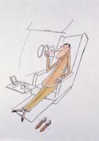 飛行機内で本を読みリラックスする男性