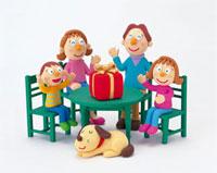 プレゼントの乗ったテーブルにつく家族 20037004378| 写真素材・ストックフォト・画像・イラスト素材|アマナイメージズ