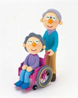 車椅子のシニア女性と車椅子を押すシニア男性