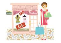 ショッピングバッグを持ってお店の前に立つ女性