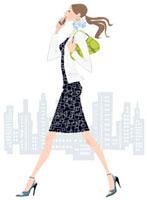 携帯電話で話しながら歩く女性