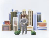 オフィス街を背景にたたずむビジネスマン