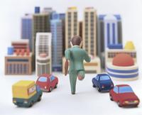 オフィス街を背景に走るビジネスマン