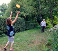 Daughter playing Frisbee with her elderly father