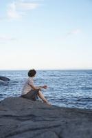 Woman sitting on a rock drinking coffee