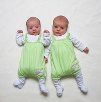Two babys in green romper suit