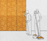Men painting wall with floral wallpaper pattern