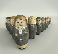 Businessmen nesting dolls lined up behind female boss