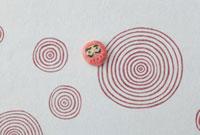 赤い渦の模様の上に達磨 20041000274| 写真素材・ストックフォト・画像・イラスト素材|アマナイメージズ