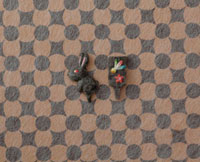 黒と茶色の模様の上に黒い兎と黒い羽子板