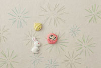 松の葉の模様の上にうさぎと達磨と鈴 20041000283| 写真素材・ストックフォト・画像・イラスト素材|アマナイメージズ