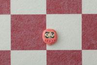 紅白の市松模様の上に達磨 20041000306| 写真素材・ストックフォト・画像・イラスト素材|アマナイメージズ