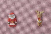 赤と白の細かい市松模様の上にサンタとトナカイ