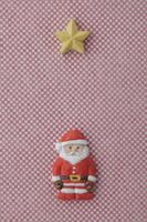 赤と白の細かい市松模様の上にサンタと星