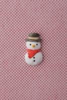 赤と白の細かい市松模様の上に雪だるま