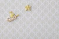 薄いベージュ色のバロック調の模様の上に天使と星