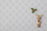薄いベージュ色のバロック調の模様の上にトナカイとひいらぎの葉