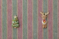 赤、黄、緑の縦縞の上にトナカイとクリスマスツリー