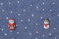 紺色の地に白い星がある背景の上にサンタと雪だるま