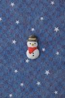 紺色の地に白い星がある背景の上に雪だるま