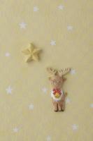 黄色地に白い星がある背景の上にトナカイと星