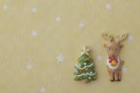 黄色地に白い星がある背景の上にトナカイとクリスマスツリー